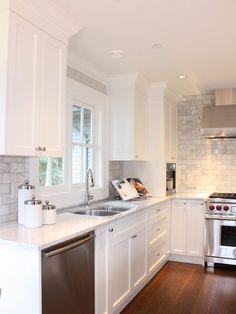 white cabnitery, stone backsplash, warm wood floors.: