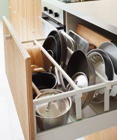 Gros plan sur un tiroir de cuisine IKEA ouvert. Casseroles et poêles sont parfaitement rangés, grâce à des séparateurs.