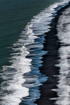 Waves hitting a black sand (volcanic)beach