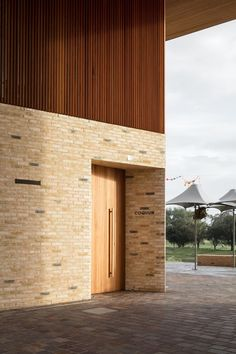 The Timber And Brick Arch Frames A Covered Space For The Community Use Timber Architecture, Public Architecture, Timber Buildings, Architecture Design, Exterior Wall Cladding, Wood Facade, Timber Staircase, Timber Windows, Brick And Wood
