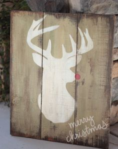Rudolf the red nosed reindeer picture on reclaimed pallet wood board. Item measures 20 x 16. The background is a muted green and is lightly sanded