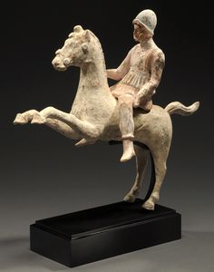 HELLENISTIC TERRACOTTA HORSEMAN ON A REARING HORSE  He wears a helmet, a short pleated tunic attached at the shoulder with straps and bushkins. Extensive polychrome remaining.  4th-3rd Century BC