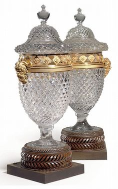 A NEAR PAIR OF RUSSIAN ORMOLU-MOUNTED CUT-GLASS AND PATINATED METAL VASES<br />SECOND QUARTER 19TH CENTURY, MINOR DIFFERENCES TO GLASS BODIES <br />Each with a lid with a vase finial above a pierced frieze with masks, on a later pierced circular base and further square plinth, very slight height differences, one glass lid restored<br />18½ in. (47 cm.) high, 7½ in. (19 cm.) wide (2)<br />