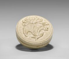 """Chinese Five Dynasties Period, glazed pottery stoneware covered box; the circular form set on a foot, the cover with carved design of a blossoming flowers in relief; D: 3 3/8"""""""