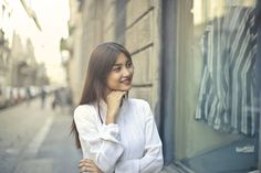 Focus Photo of Woman in White Long-sleeved Dress Standing at the Front of Gray Building  Free Stock Photo