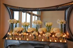 All white entrance table to a wedding. Vases filled with lilies and hydrangea.