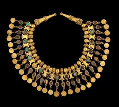There are delicate inlaid gold personal ornaments worn by the nomadic elite. All the artefacts showcase the trading and cultureal connections of Afghanistan and how it benefited from being on an important crossroads of the ancient world.  Ornament for the neck of a robe from Tillya Tepe, Tomb V. Dated from 1st century BC-1st century AD and made from gold, turquoise, garnet, and pyrite.