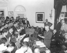 President Harry S. Truman (standing behind desk) announces the surrender of Japan, ending World War II, August 14, 1945.