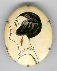 Celluloid pin of a flapper, 1920's. Are those pearls around her neck?