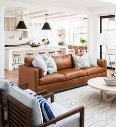 idée cuisine ouverte sur le salon, façade cuisine et ilot central blanc, avec des tabourets en bois, suspensions noires, canapé en cuir, chaises en bois avec coussins d assise gris, table basse en bois