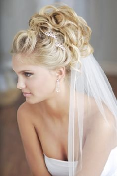 Wedding updo, with a few pieces hanging down in the back and a crystal clip pushed into the bun, on the side