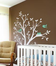 Árbol con pajaritos decorando el cuarto del bebé.
