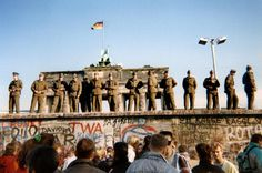 East German border guards stand on a section of the Berlin wall with the Brandenburg gate in the background on November 11, 1989 in Berlin. On November 9, Gunter Schabowski, the East Berlin Communist party boss, declared that starting from midnight, East Germans would be free to leave the country, without permission, at any point along the border, including the crossing-points through the Wall in Berlin