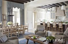An open floor plan allows the kitchen, dining area and a gathering space to seamlessly blend together; walls are covered in Benjamin Moore's Carrington Beige. Three large pendants from Circa Lighting illuminate the island; traditional barstools are from Zentique. A pair of rugs from Mrs. Howard and four large armchairs from Hickory Chair create an inviting seating area.