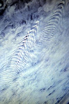 Kelvin Wakes clouds viewed from the Space Shuttle. These clouds formations are caused when a cloud system runs across mountains or tall hills, which disturb the cloud layer from below. (STS 61-A, October-November 1985. Picture #61A-31-066.)