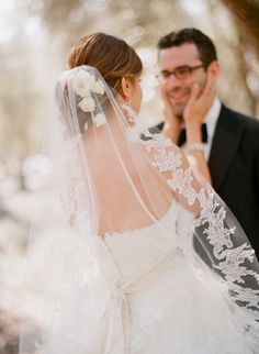 The bride wore her hair in an elegant chignon embellished with white florals and a beautiful embroidered veil featuring lace details. #veil Photography: Elizabeth Messina