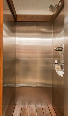 This ultra-sleek shower has wrap around stainless steel walls, simple fixtures, natural wood plank flooring, and is open to above.
