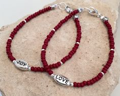 """Red bracelet made with Czech glass seed beads, sterling silver round beads, a """"Love"""" or """"Joy"""" word bead and a sterling silver trigger clasp by BeadedMoonbeams on Etsy"""