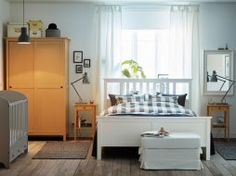 A light medium sized bedroom furnished with a white bed for two combined with bedside tables and a wardrobe in yellow stained solid pine.