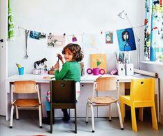 Original zona de estudio infantil con sillas de estilo ecléctico y una cuerda para colgar los dibujos de los niños.