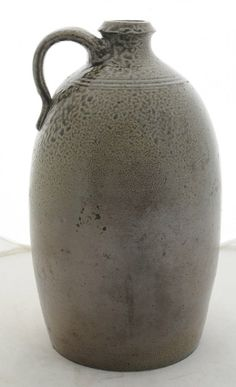 """Two Pieces North Carolina Pottery storage jar with lug handles, dark green alkaline glaze, incised """"3"""" angled on shoulder, possibly Catawba Valley, 13 in., [3 in. hairline crack at rim, large glaze anomaly at handle, several chips at base;] ovoid salt glaze jug with sharp collared rim and strap handle, reddish-green color and incised line decoration at shoulder, possibly Randolph County, 11 in."""