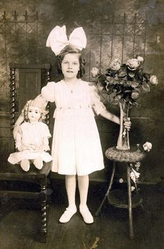 Girl with her doll, a vase of flowers, and a giant hair bow.