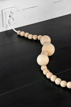 Perles en bois pour dissimuler les fils  http://www.homelisty.com/cacher-ranger-cables-fils-prises-electriques/