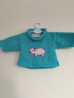 Piglets are my favourite, so I just had to design a little one to put on front of this pull over. Cute pink piglet on a teal coloured background. The hem and sleeves are worked in garter stitch, it's a roll neck worked in reverse stocking stitch. Perfect to pull on for those chilly