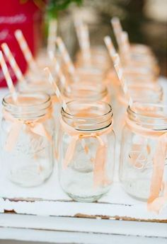 Adorable Mason jars with peach and white paper straws! Just perfect for serving up cocktails at a rustic wedding.