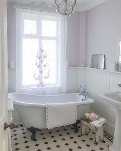 This farmhouse bath has all the right elements: claw foot tub, chandelier, bead board and retro tile floor