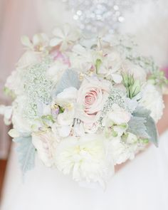 The subtle hints of pink in Jennifer's soft, textured clutch of peonies, roses, and variegated phaleonopsis orchids complemented the rosy velvet ribbon on her gown.