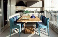 Um degradê de azuis nas cadeiras Orquídea, design de Rejane Carvalho Leite, junta-se à mesa Corten, do designer Silvio Romero, no terraço gourmet. Projeto da arquiteta Fabiana Avanzi