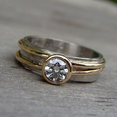 This ring has just the right balance of quirky character and traditional elegance. It features a 4.5mm moissanite (equivalent in size to a 0.33 carat diamond) set in a 14k yellow gold tapered bezel on a 5mm wide layered band (950 Palladium with a hand textured finish topped with two asymmetrically placed 1mm strips of lightly hammered and polished 14k yellow gold). All of the metal used in the construction of this ring is from recycled sources. Please allow 3-4 weeks for fabrication of your…