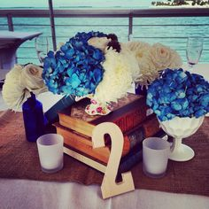 Shabby chic / Vintage inspired centerpiece. Books, milk glass vases, vintage teacups, vintage vases, burlap. Flowers & design by Soiree Key West. Www.soireekeywest.com