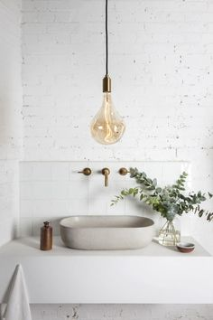 tala light fixture in pristine-white industrial-mod bathroom.