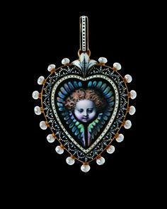 Heart formed hair locket by Carlo Giuliano. The face of the cherub is created with powder blue and pink enamel surrounded by a pattern of complex blue and white enamel in the revival style of the Art of Hans Holbein. Threads of gold run through the hair of the cherub.