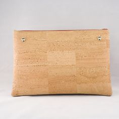 Jelinek Cork | Menina Clutch Take the spirit of Portugal with you anywhere you go with the Menina Clutch. Iconic figures, historic landmarks, and vibrant Portuguese culture are all represented in the design of this funky and flirty clutch. When in need of a more refined look, simply flip the clutch over for a more traditional Harmony cork fabric pattern. Need to go hands-free? Attach the included strap for easier carrying. The Menina Clutch is handmade in Portugal with premium cork fabric.