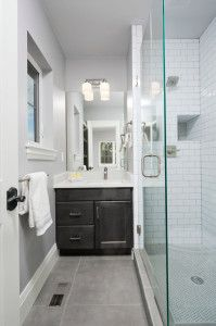 Guest Bathroom Ideas: Large gray porcelain floor tiles 24x24 and classic white subway tile with gray penny rounds in niche and shower pan.  Cabinet has a graphite stain.  Rondec Schluter was used.