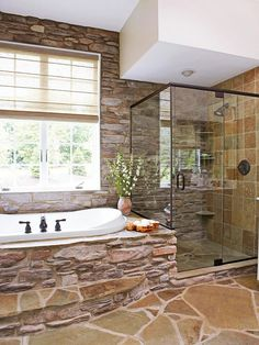 Rustic Retreat  In a home designed with lakeside views and rustic cottage influences, natural stonework was only befitting of the master bathroom