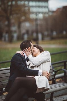 The bride and groom kissing on a bench near Faneuil Hall in Boston, Massachusetts | Wedding Photography