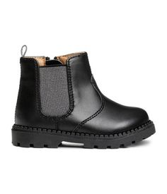Black. Chelsea boots in imitation leather with an elastic panel at one side and zip at the other. Loop at back, faux fur lining and insoles, and chunky
