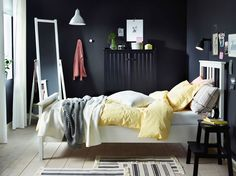 White bed with a white and yellow bedding, and black sideboard and a step stool.