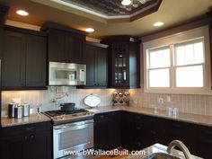 Dark cabinets, light granite countertops and grey vertical subway tile for backsplash