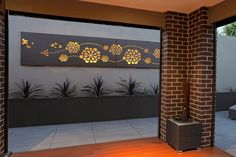 Outdoor living area with feature wall art 'Flower wave' custom lightbox by Entanglements