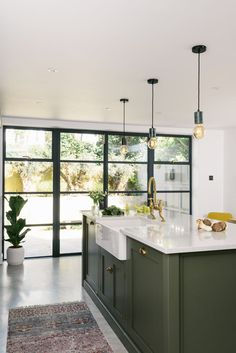 A classic Belfast sink was fitted into this chunky Shaker kitchen island painted in dark sage green, with an aged brass Ionian tap by deVOL and Perrin and Rowe. Above the island are three simple hanging pendant bulbs, a cool contemporary styling choice that also still feels understated.