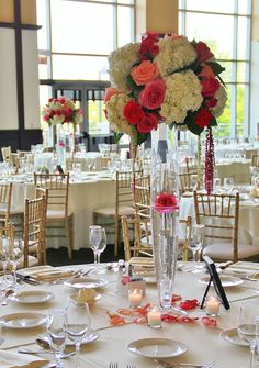 Centerpieces for a wedding at Harry Carey's in Lombard. White hydrangeas, pink Floyd roses, dark fushia spray roses, burgundy and green hanging ameranthus, coral amsterdam ross, salal and hot pink roses on a DaVinci Glass vase.