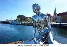"Helsingor, Denmark - 06 May, 2018: Sculpture ""Han"" of naked young man siting on stone gazing at sea by Michael Elmgrin and Ingar Dragset, Sculpture repeats pose of Mermaid in Copenhagen"