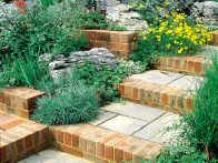 A mix of stones and bricks creates a rural look and feel for a flight of steps that links a lower-level garden terrace with an upper patio area.