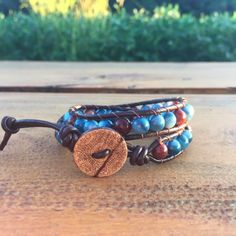 """This double-wrap bracelet features round blue and natural-toned jasper beads with subtle, beautiful variations, accented with chocolate brown """"cat's eye"""" glass beads. The cord is … Brown Cat, Blue Brown, Chocolate Brown, Jasper, Glass Beads, Cord, Brown Leather, Eye, Natural"""