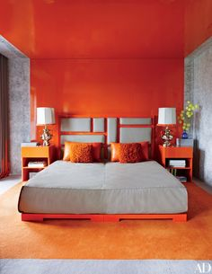 In the guest room of a Hong Kong apartment, the bed—another one-off by the home's designer, Mattia Bonetti—is positioned within a swath of orange lacquer that serves as a virtual canopy. The designer padded the headboard with the same gray leather used for the bedspread, and the lamps and custom-made nightstands are also his work.